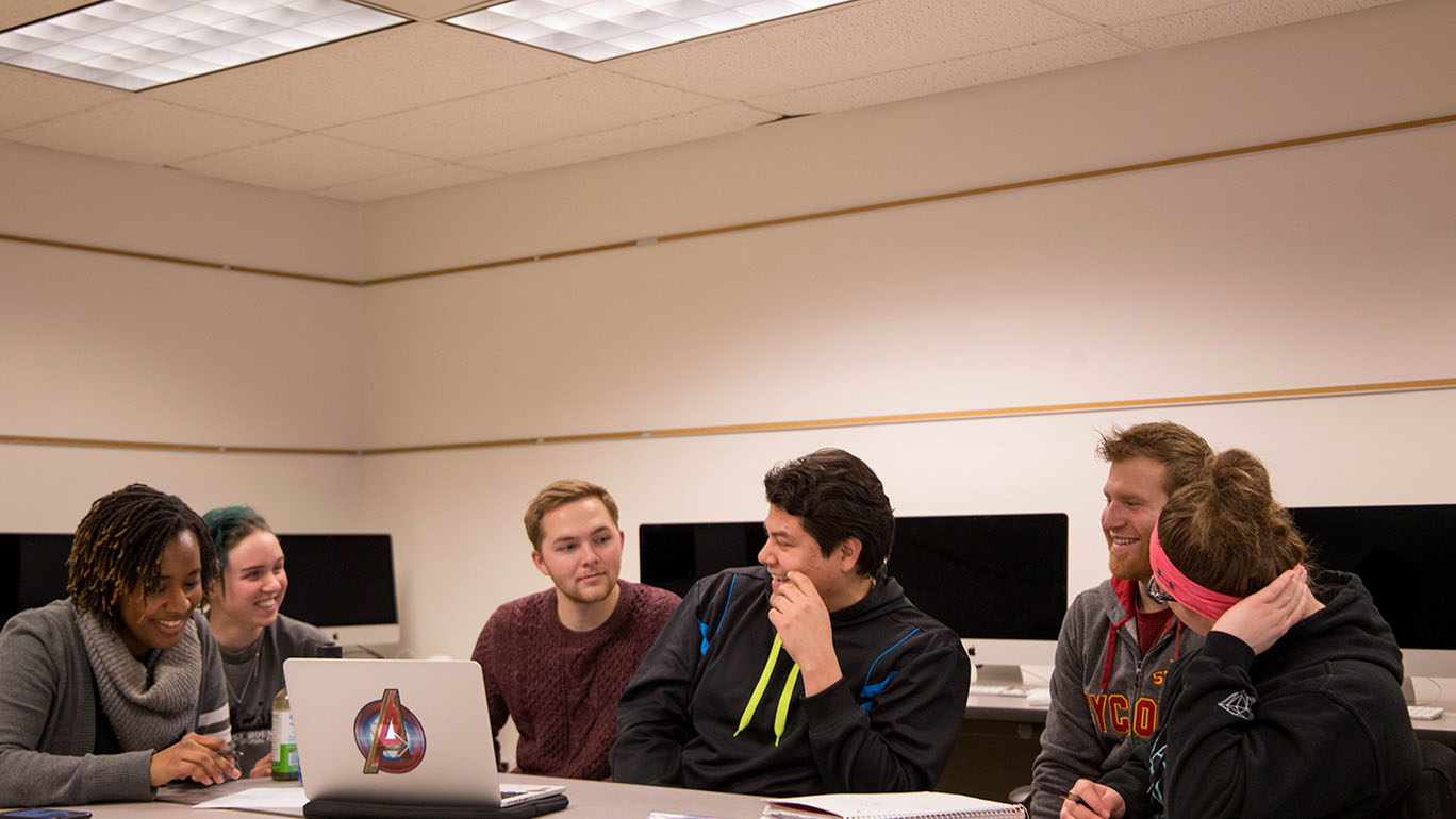 Three female and three male students meet in a computer lab around a computer.