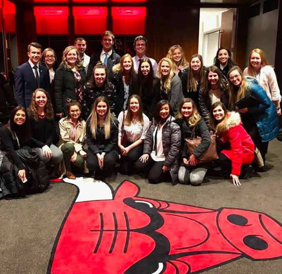 A group of students in winter coats huddle for a group photo with a big Chicago Bulls logo in front of them on the floor.