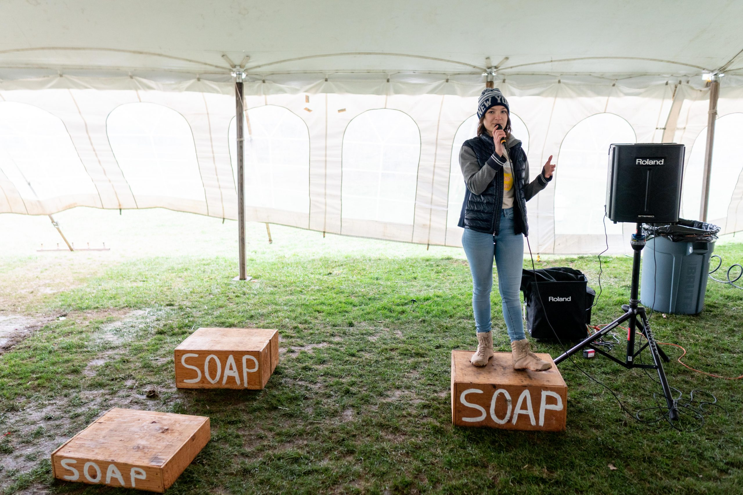 woman stands on a soap box with a microphone in hand