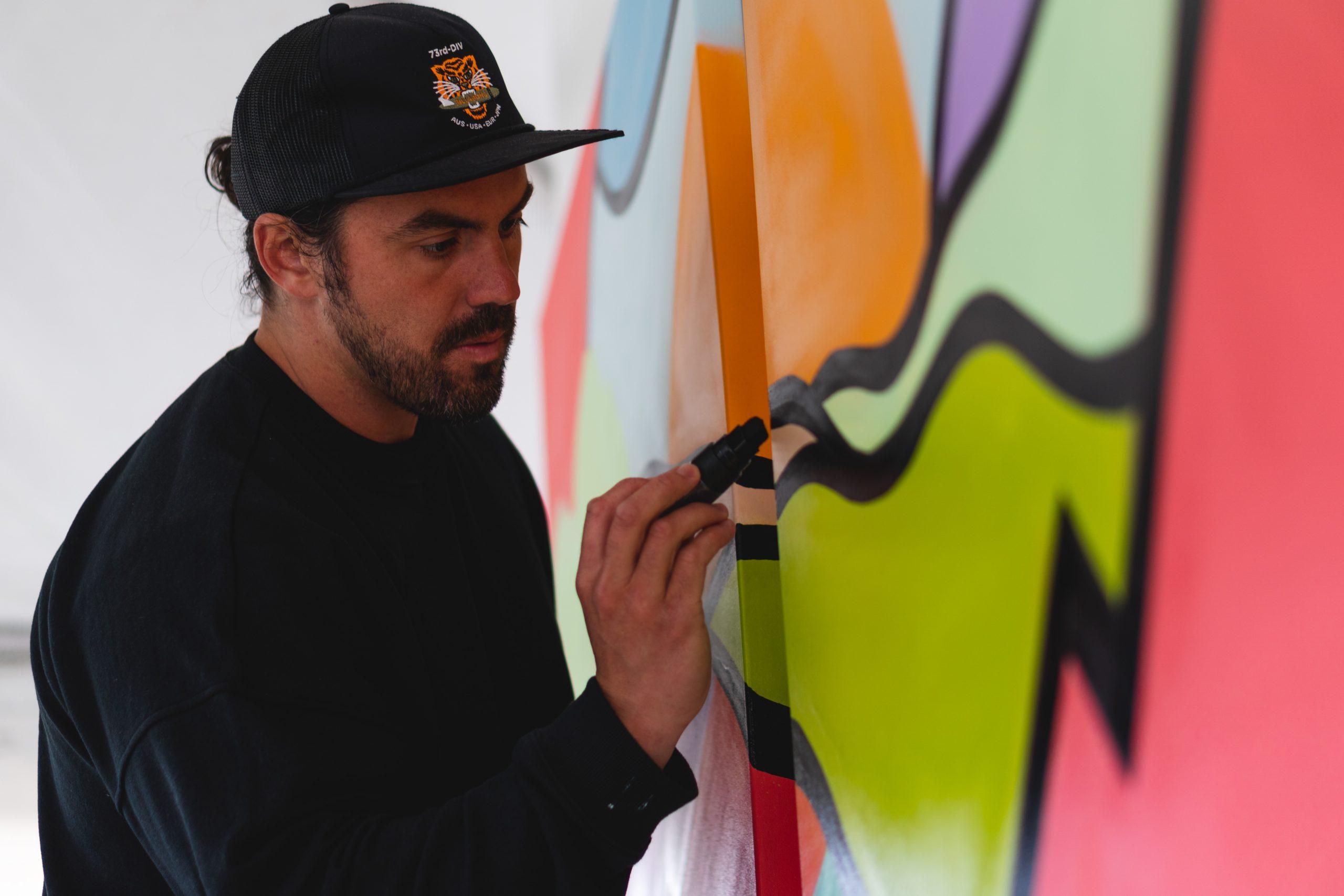 an artist paints black lines on a colorful canvas