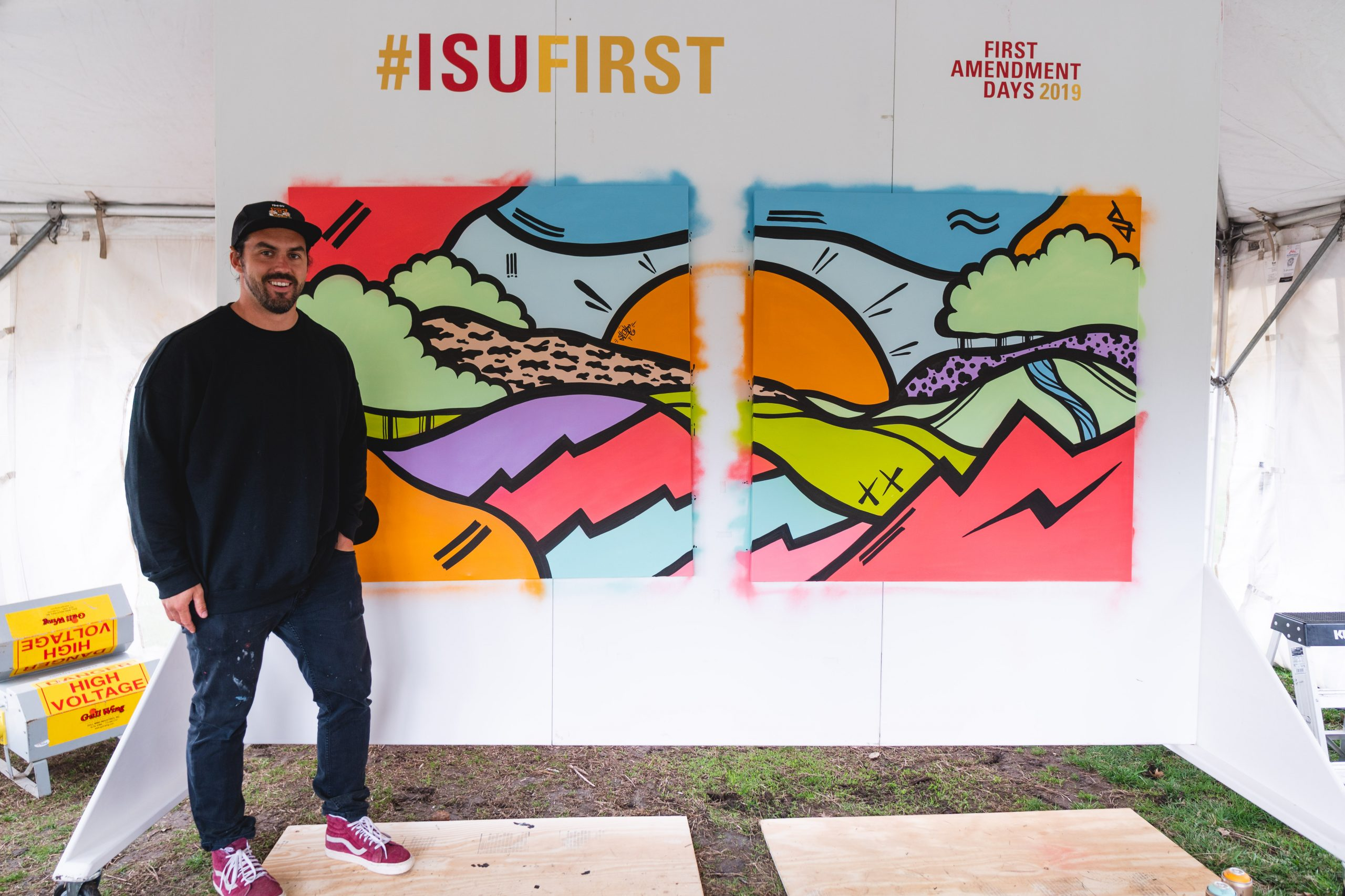 an artist stands in front of a colorful diptych in fluorescent colors