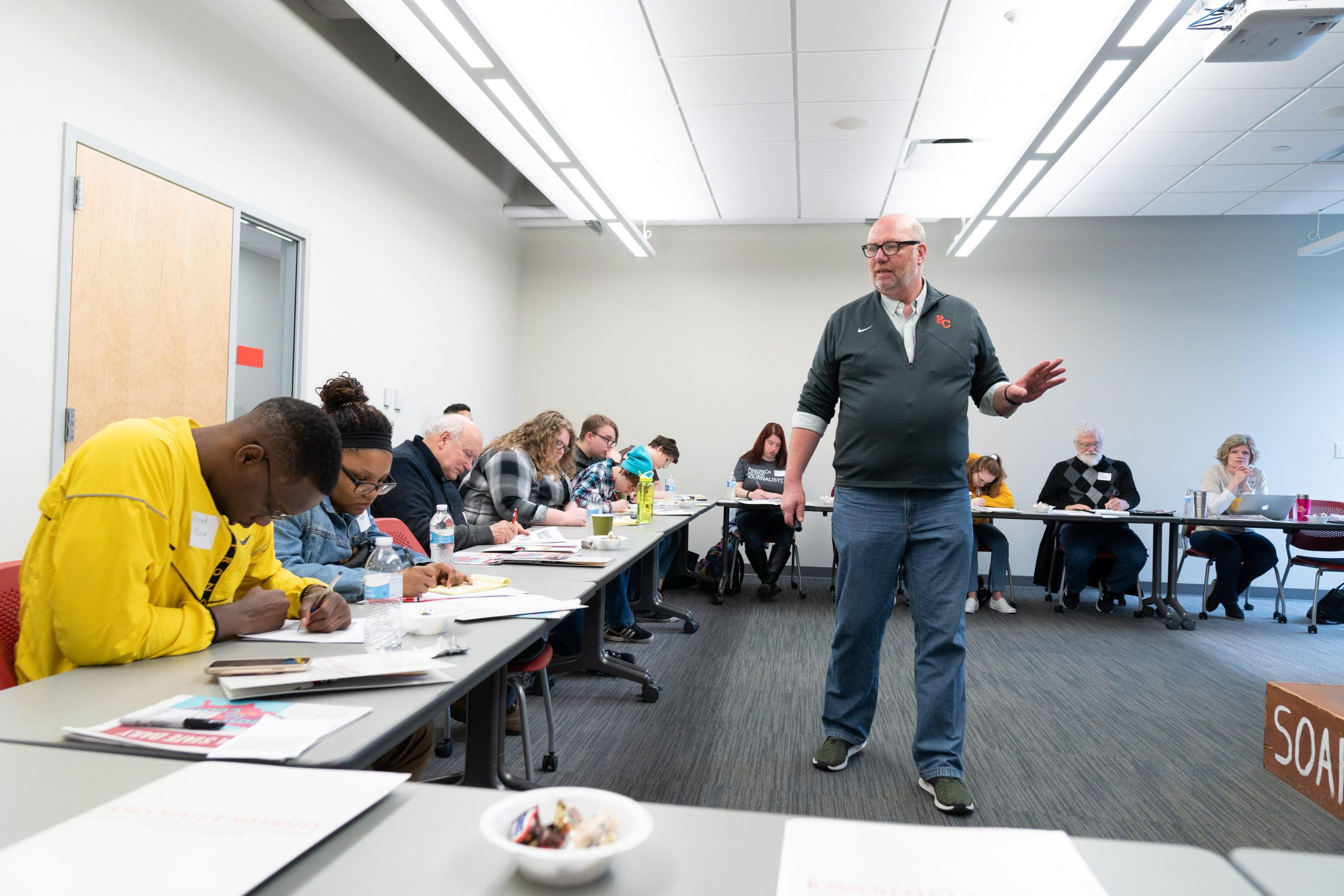 a man walks around a room filled with people during a workshop