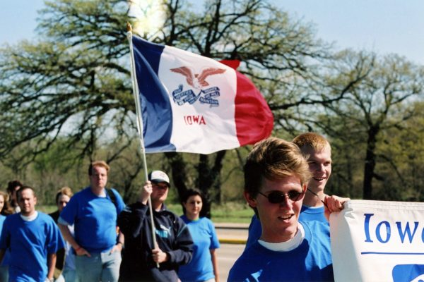 students marching with flag of Iowa