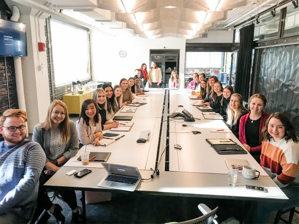 students gathered around a conference table